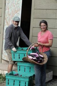 two people holding eggplants