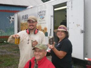 three people hold jars