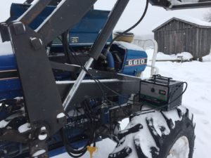 The author attempts to get his tractor used for feeding livestock running in below zero temperatures, with a block heater, and a battery booster/charger.