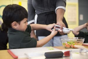 Pre-K student squeezing lime juice for the salsa. Photo by Nancy Borowick.