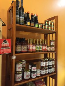 A shelf dedicated to a wide variety of locally produced foods stands near the front counter of the grocery.