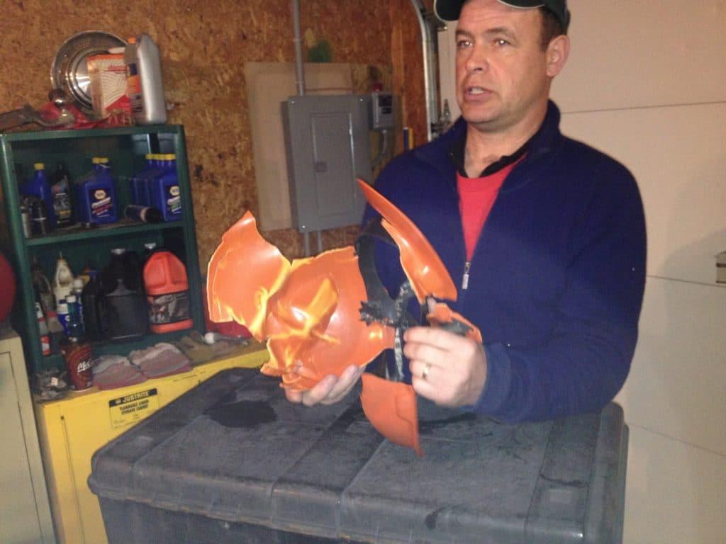 person holding damaged helmet