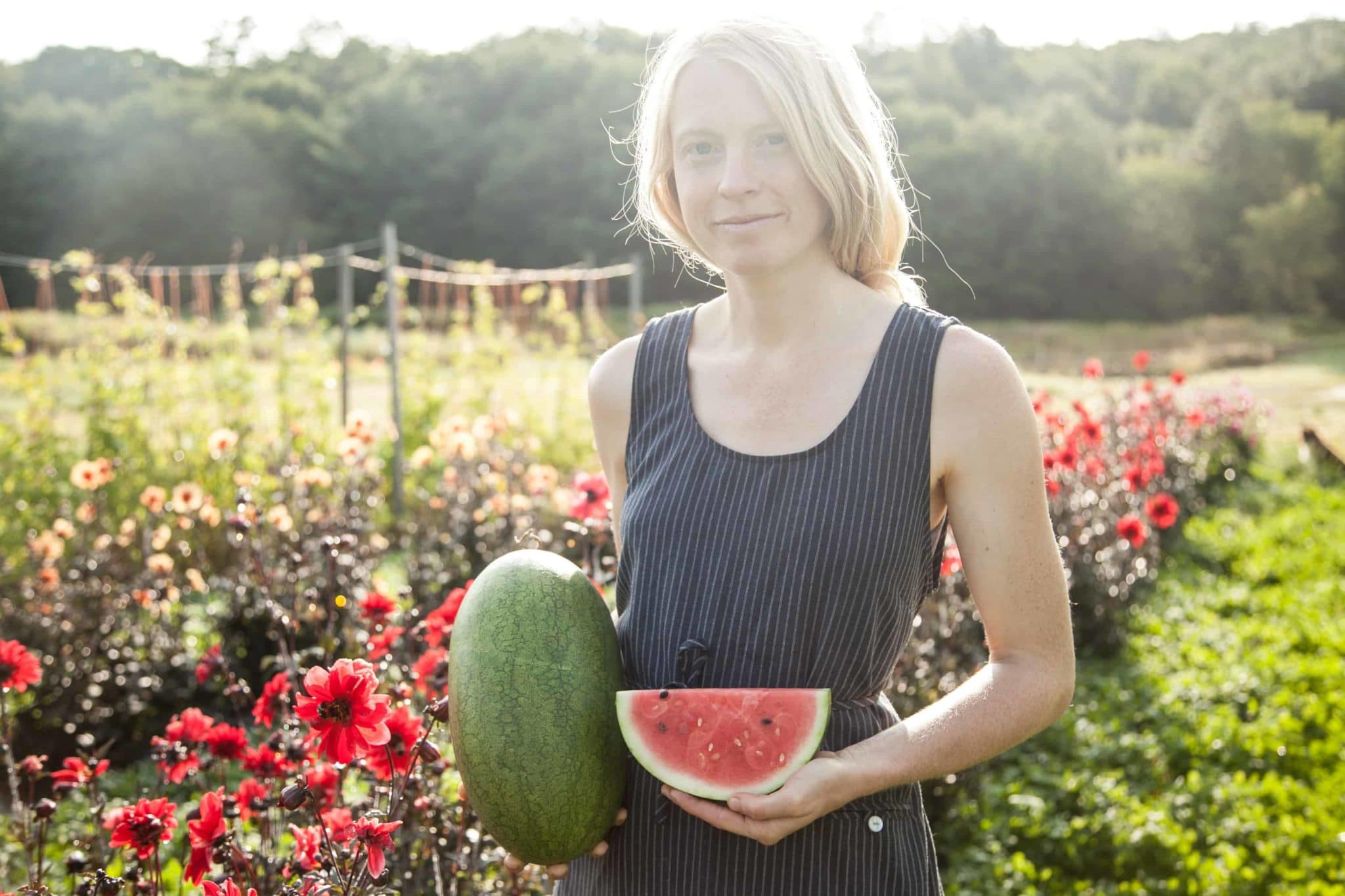 person standing in a field holding a watermelon