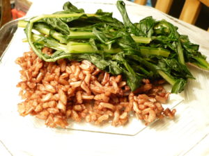 A plate of Wehani rice, with sauteed dandelion greens.