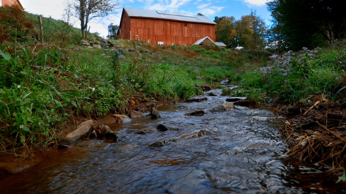 creek in front of red barn