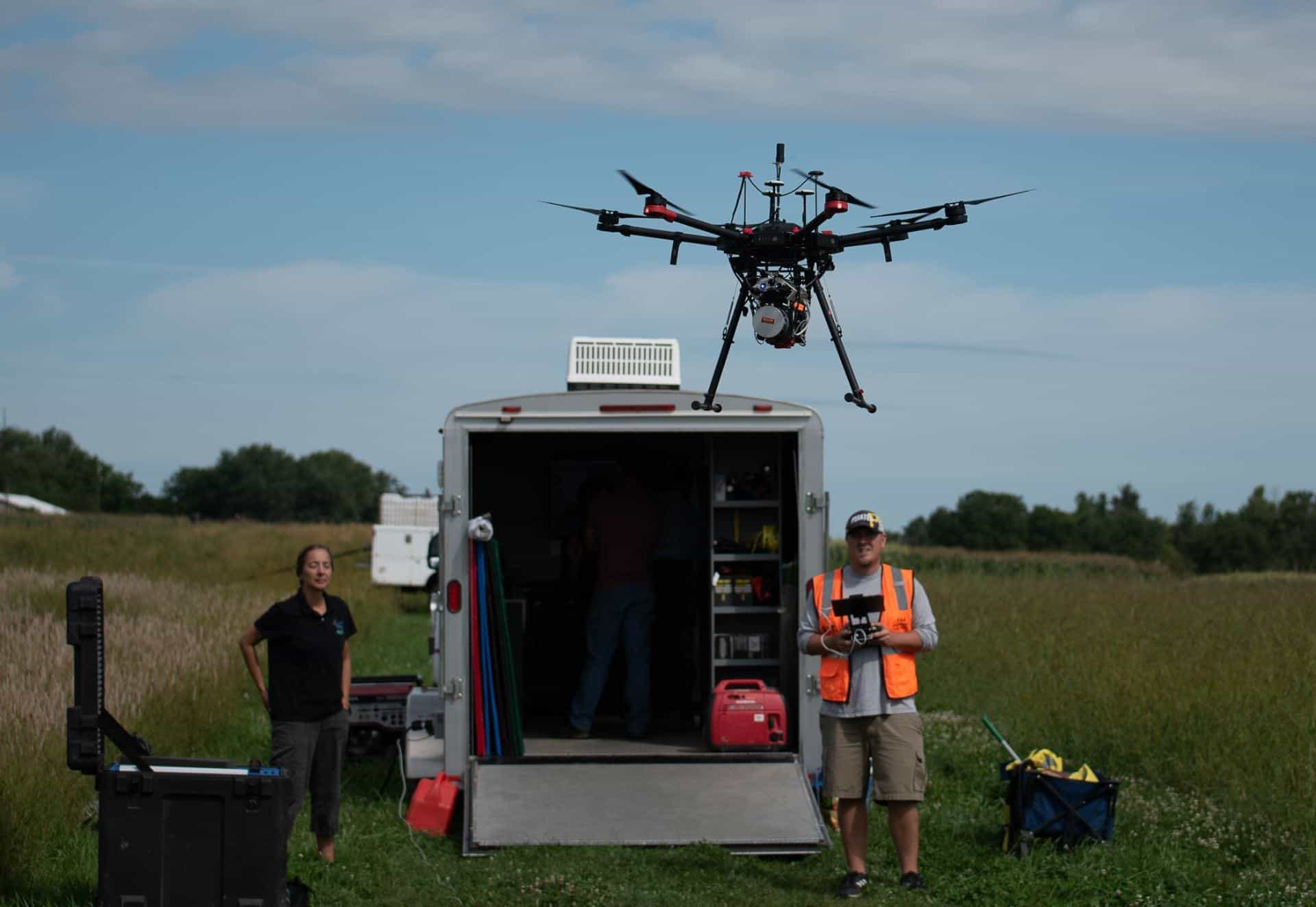 two people standing next to a trailer with a drone above