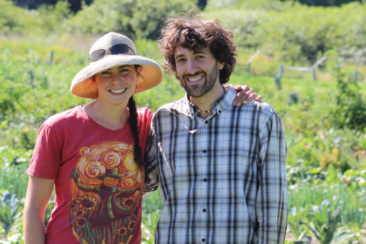 Two people with their arms around each other smile in a field.