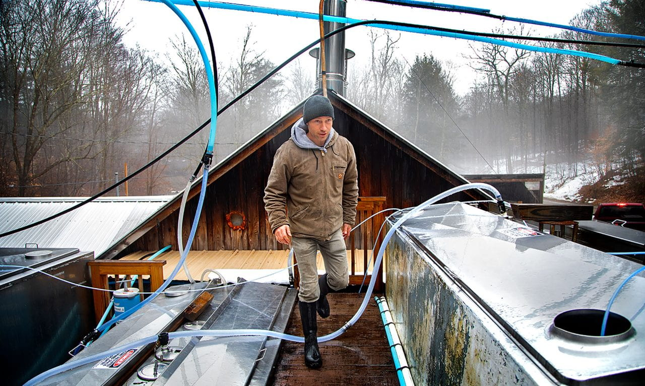 A person stands between two metal tubs connected with plastic pipes.