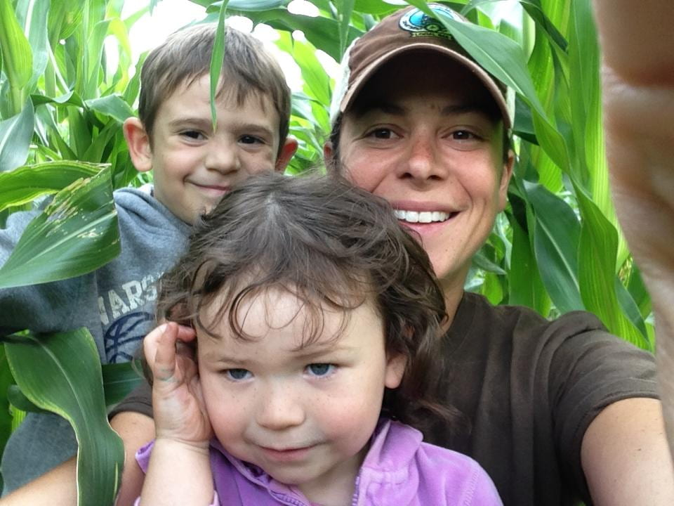 An adult and two children in a cornfield.