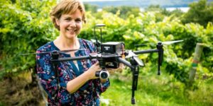 Justine Vanden Heuvel holds the imaging system in a vineyard