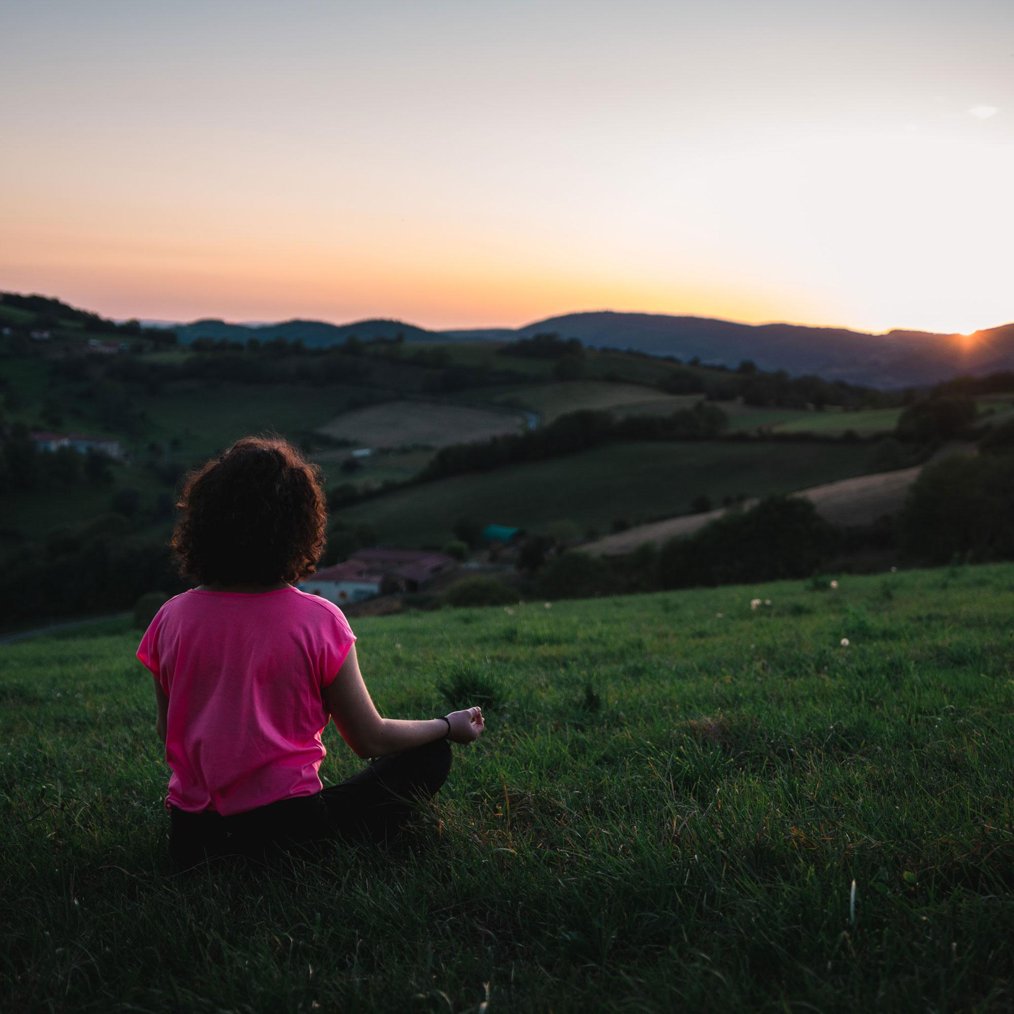 woman-meditating-field-hills