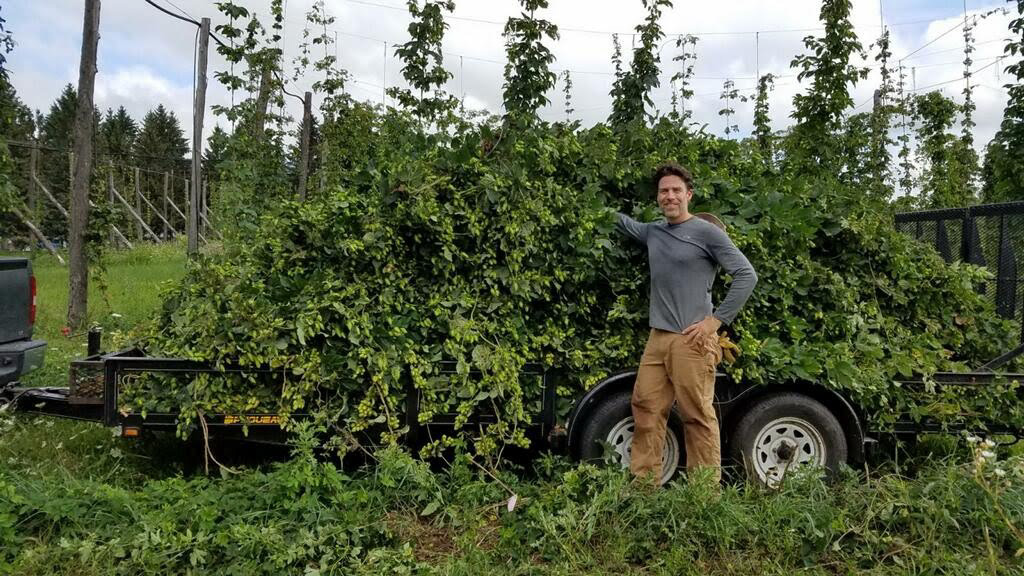 Smart Farming Team participants and Bineyard owner, Chad Meigs poses with a beautiful hop harvest.