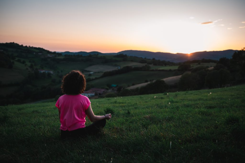 woman-meditating-field-hills-full